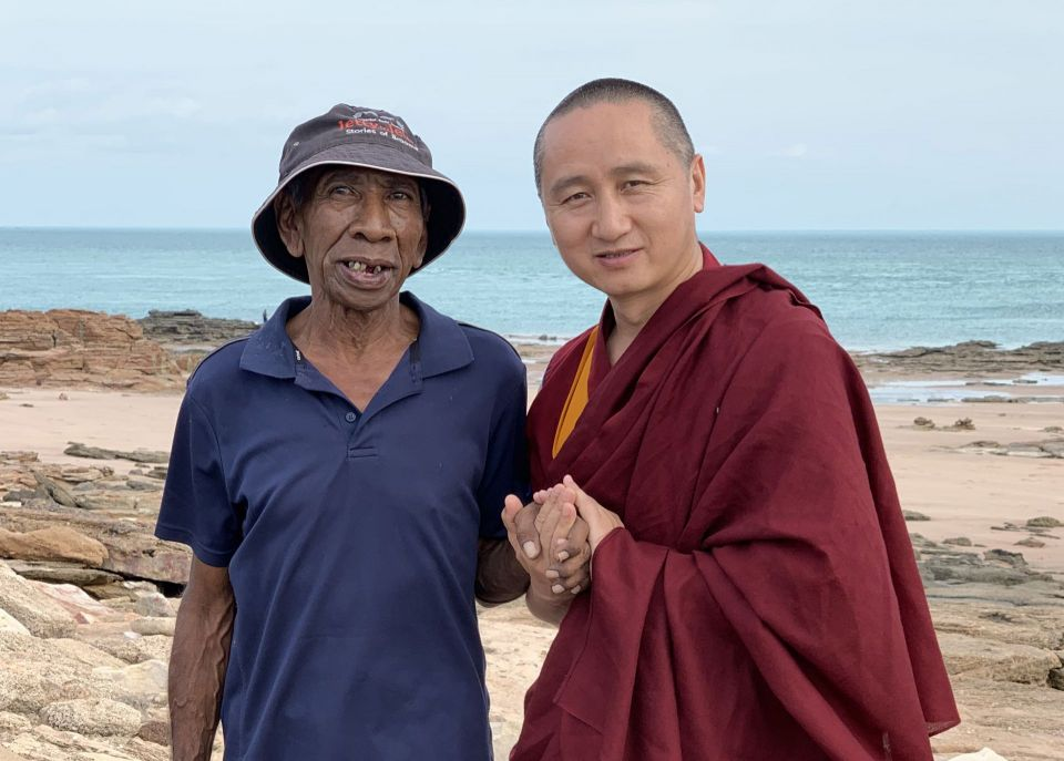 Jimmy Edgar and Geshe Tenzin Zopa standing together with hands clasped looking into the camera while standing on a beach with the ocean behind them.