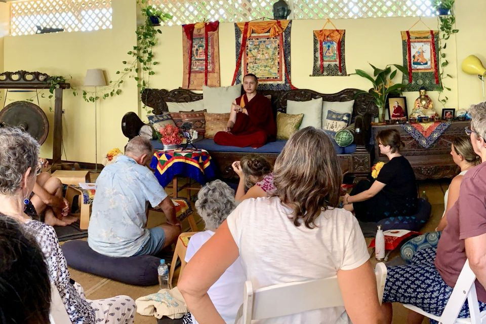 Geshe Tenzin Zopa seated on a beautiful wood couch in front of a wall decorated with plants and thangkas teaching to a room of students seated on cushions and chairs.