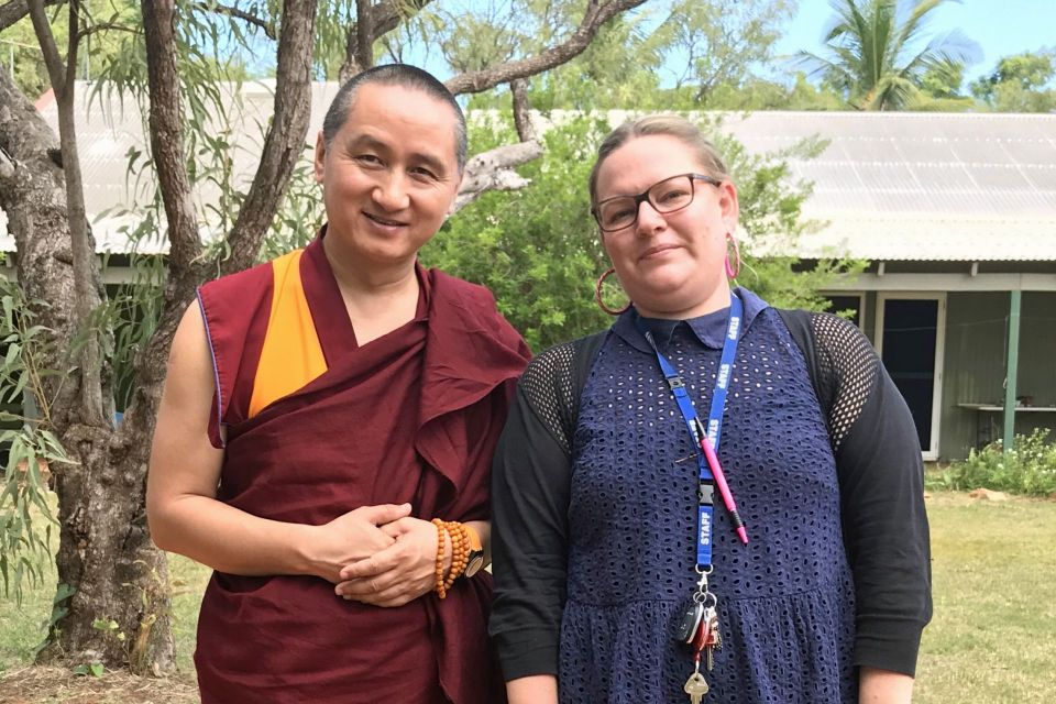 Geshe Tenzin Zopa standing next to Phoebe as they pose for the camera in front of a low building and trees and a bush.