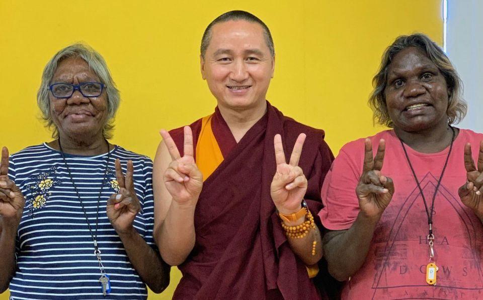 Geshe Tenzin Zopa standing between Kathleen wearing a blue and white striped shirt and Jemma wearing a pink shirt all three smiling and holding all of their hands up after having made peace signs.