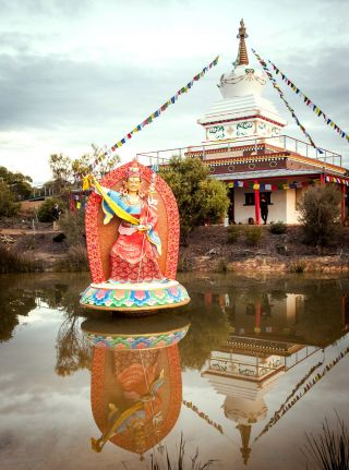 Padmasambhava statue and stupa with reflections on a very still pond. Photo by George Manos.
