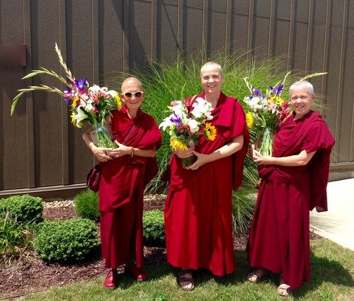 three nuns holding flowers