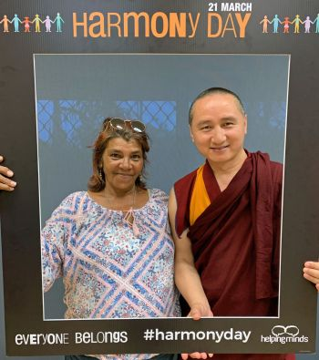 Natalie and Geshe Tenzin Zopa posing in a photo booth style photo while holding up and standing inside of a giant picture frame that says harmony day on it.