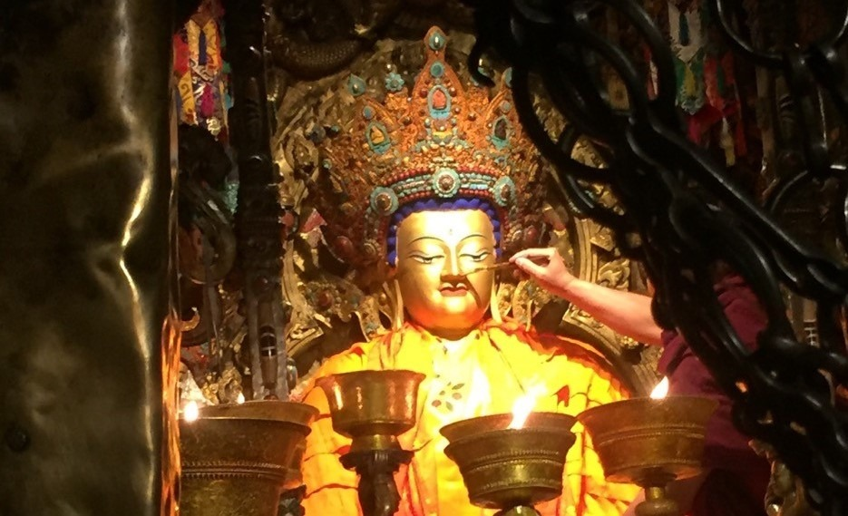 Gold leaf being applied to the Jowo Buddha statue in Tibet.