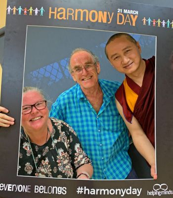 Sandy and Neil and Geshe Tenzin Zopa posing in a photo booth style photo while holding up and standing inside of a giant picture frame that says harmony day on it.