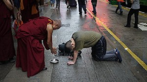 Lama Zopa Rinpoche making offerings to a street person in Hong Kong, 2010.