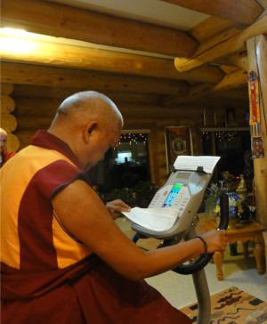 Lama Zopa Rinpoche reading texts while on his exercise bike, US.