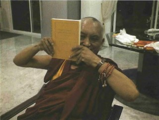 Lama Zopa Rinpoche with a print version of the Golden Light Sutra. Photo by Lee Chung Han.