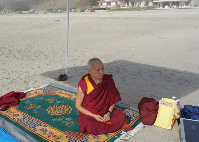 Rinpoche on the beach doing the prayers and mantras for blessing the ocean and creatures within while most of the Sangha are in the water moving the mantra boards through the waves, Califorania, October 26, 2013. Photo by Ven. Roger Kunsang.