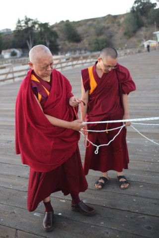 Lama Zopa Rinpoche holding ropes attached to mantra boards blessing beings in the ocean, Aptos, California, September 14, 2013. Photo by Ven. Thubten Kunsang.