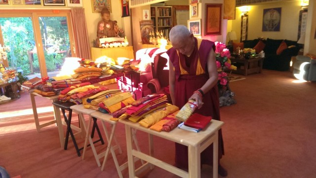 "Lama Zopa Rinpoche sorting through his texts, Kachoe Dechen Ling, September 13, 2013 ""All these we carry in four big heavy suit cases everywhere we go!"" Ven. Roger comments."