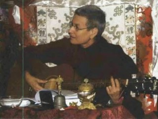 Ven. Nyingje strums the guitar and sings from her songbook following the successful completion of the December Vajrayogini Retreat