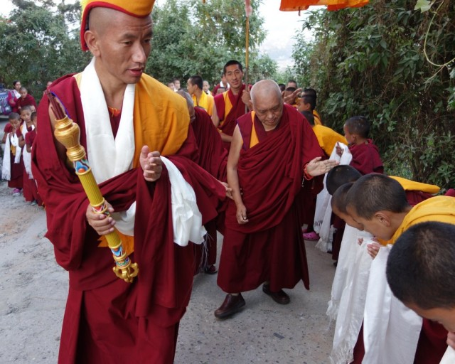 Lama Zopa Rinpoche being led by the Kopan gegu as Rinpoche is greeted by Kopan monks, Nepal, November 22, 2013. Photo by Ven. Roger Kunsang.