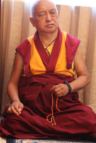 Lama Zopa Rinpoche doing prayers, sitting on the floor in his room at Kachoe Dechen Ling, Aptos, California. November 2, 2013. Photo by Ven. Roger Kunsang.