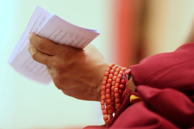Lama Zopa Rinpoche holding a text, Amitabha Buddhist Centre, Singapore, February 2010. Photo by Miss Seow.