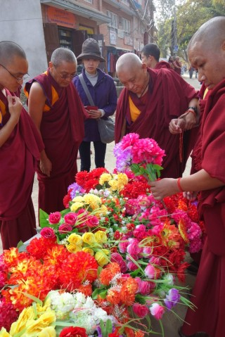 Lama Zopa Rinpoche buying plastic flowers while doing circumambulation at Swayambunath with Khen Rinpoche Geshe Chonyi and Geshe Jangchub, Kathmandu, Nepal, November 24, 2013. Photo by Ven. Roger Kunsang.
