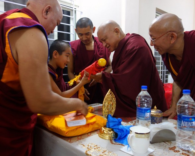 Lama Zopa Rinpoche offering gifts to Domo Geshe Rinpoche after arriving for dinner at Domo Labrang, Sera Je Monastery, India, January 2014. Photo by Ven. Roger Kunsang.