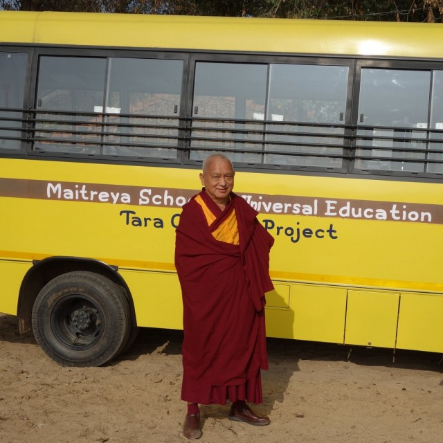 Lama Zopa Rinoche in front of the new bus that serves children attending the Maitreya School and who are part of the Tara Children's Project, January 2014. Photo by Ven. Roger Kunsang.