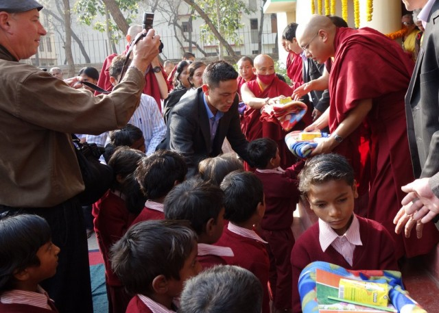 His Holiness the Karmapa offers gifts to Maitreya School children, Bodhgaya, India, January 31, 2014. Photo by Ven. Roger Kunsang.