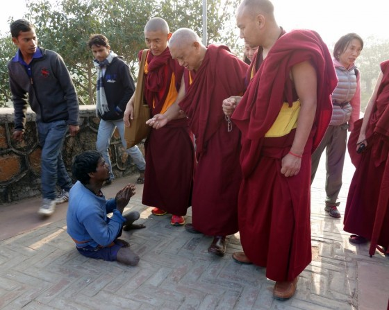 Lama Zopa Rinpoche offering money to the beggars on the way up to Vulture's Peak. Rinpoche asks them to recite OM MANI PADME HUM, India, February 2, 2014. Photo by Ven. Roger Kusang.