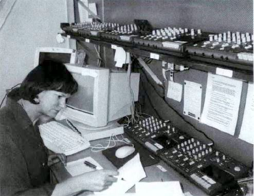 Anne Pottage, database and quality control volunteer, sits below a bank of high-speed tape players. Photo by Greg Sneddon.