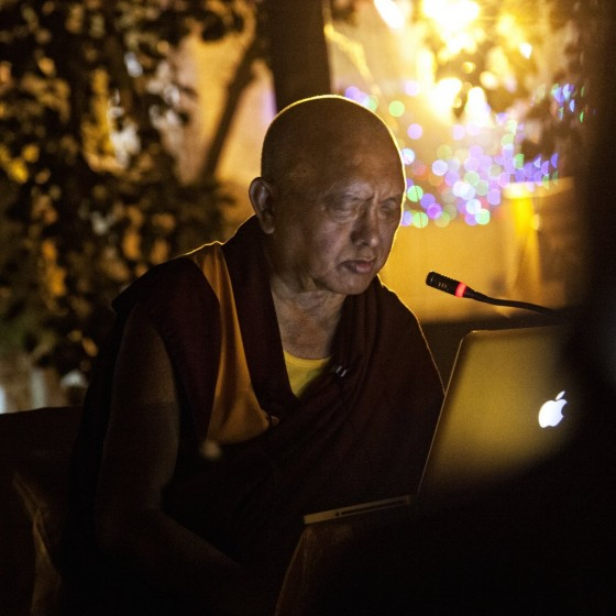 Lama Zopa Rinpoche reading Golden Light Sutra at Mahabodhi Temple, Bodhgaya, India, March 2014. Photo by Andy Melnic.