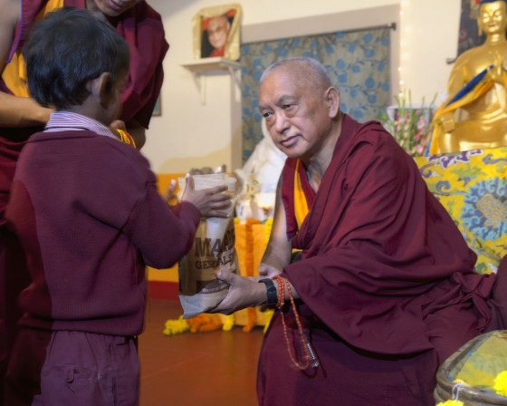 Lama Zopa Rinpoche offering gifts to children from Maitreya School and Tara Children's Project at Root Institute, Bodhgaya, India, March 2014. Photo by Andy Melnic.
