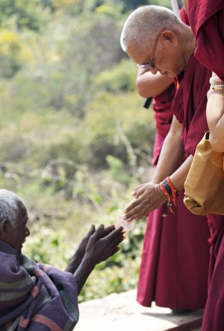 Lama Zopa Rinpoche making an offering to a beggar on the way up to Vulture's Peak, India, March 2014. Photo by Andy Melnic.