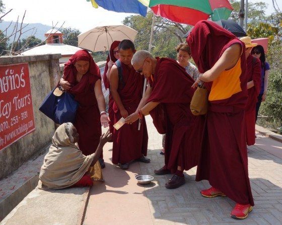 Lama Zopa Rinpoche  visiting Rajgir and offering to the beggars on the way up to Vulture's Peak, India, March 2014. Photo by Ven. Roger Kunsang.