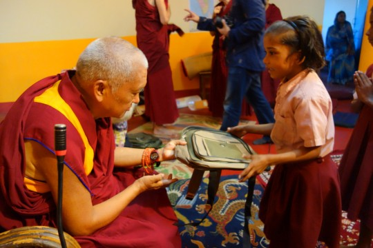 Lama Zopa Rinpoche offering rucksacks to young Maitreya School student, Bodhgaya, India, March 2014. Photo by Ven. Roger Kunsang.