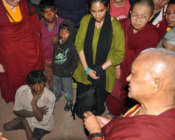Lama Zopa Rinpoche teaching beggar, Bodhgaya, India, March 2014. Photo by Ven. Sarah Thresher.