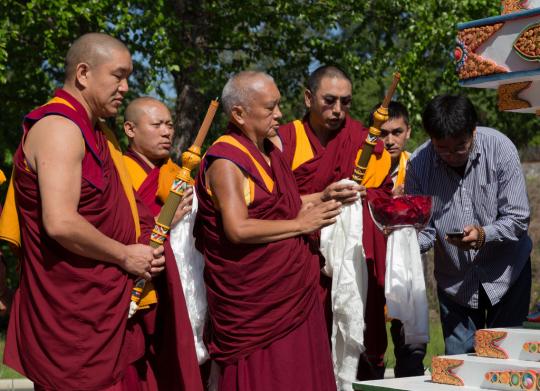 Lama Zopa Rinpoche blessing the Kadampa Stupa at Kadampa Center, Raleigh, North Carolina, US, May 2014.  Photo copyright David Strevel.