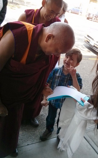 Lama Zopa Rinpoche being offered the hand-traced Heart Sutra by Dechen Bloom, Portland, Oregon, US, April 2014. Photo by Mandala.