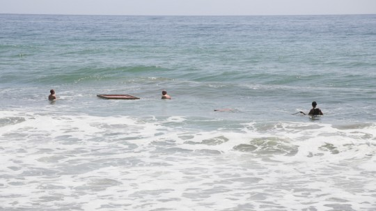 Sangha with the Namgyälma mantra boards in the Pacific Ocean, California, May 2014. Photo by Ven. Thubten Kunsang.