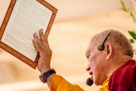 "Lama Zopa Rinpoche with the card ""Compassion is of the Utmost Need,"" created by FPMT Education Services, Land of Medicine Buddha, California, September 2013. Photo by Chris Majors."