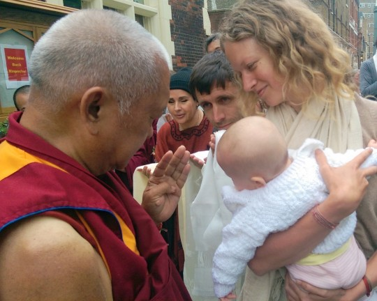 Lama Zopa Rinpoche blessing a baby upon arriving at Jamyang Buddhist Centre, London, UK, July 2014. Photo by Ven. Roger Kunsang.
