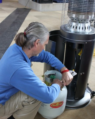 Harald Weichart helps change the fuel for the space heaters at CPMT 2014, Great Stupa of Universal Compassion, Australia, September 16, 2014. Photo by Laura Miller.