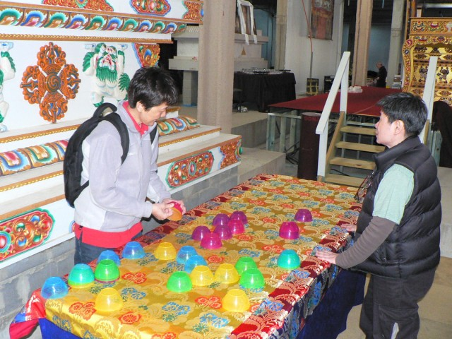 Pik Pin Goh and Sally Ong from Losang Dragpa Centre beginning to set up water bowls in front of the Guru Rinpoche statue in the Great Stupa, Australia, September 12, 2014. Photo by Laura Miller.